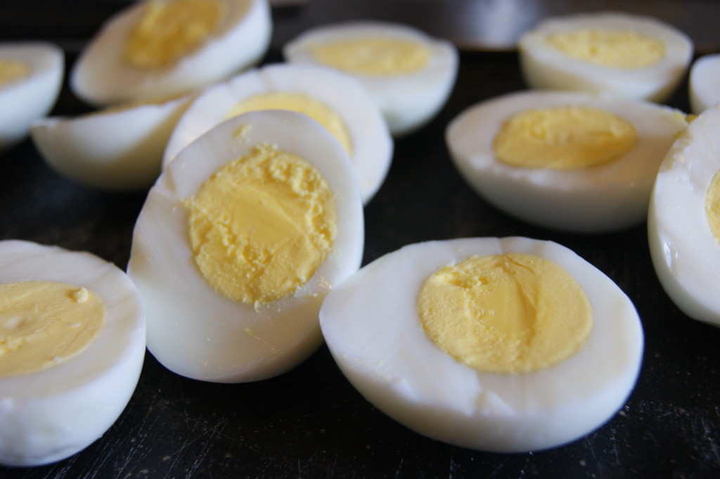 Place eggs in a large pot and cover by one inch with cold water.  Bring to a simmer over medium-high heat, then cover.  Cook for 5 - 7 minutes, remove from heat and leave covered for another 5 minutes.  Drain, cool in ice water and peel.