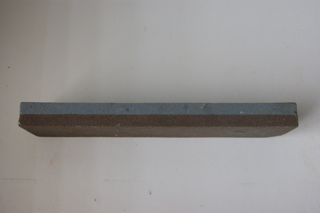 A whetstone with a rough and fine grit.  The grey side is the rough grit and the side you should start with.